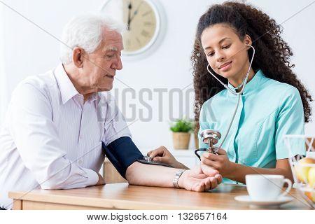 Female nurse taking elderly patient's blood pressure.