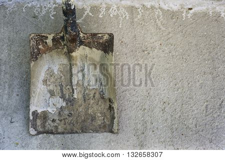dirty spade on background of the concrete surface