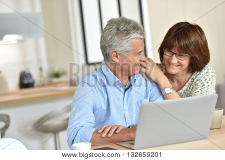 Senior couple using laptop computer at home