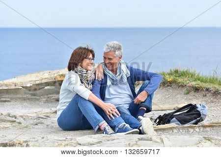 Senior couple on rambling day sitting by cliff