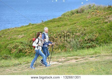 Senior couple walking on hiking track by the coast