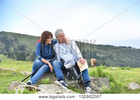 Senior couple of hikers relaxing on rocks