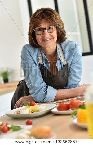 Senior woman in home kitchen preparing dish