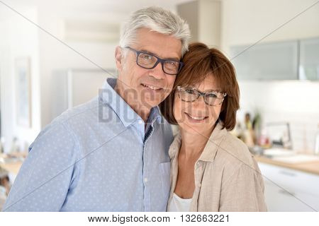 Portrait of happy senior couple standing in kitchen