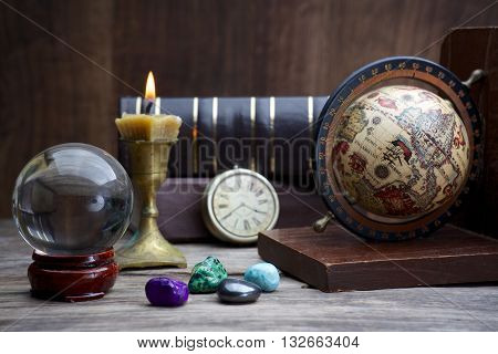 Ancient astrology. Old astrology globe and books with candle