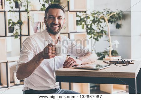 Enjoy the best coffee in town! Cheerful young man holding cup of coffee and looking at camera with smile while sitting in cafe