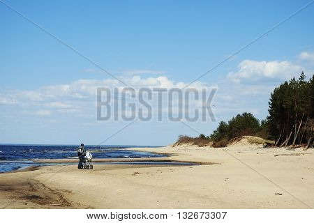 Baltic sea cost. Walking man with carrage
