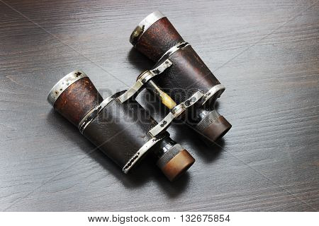 Old field binoculars on a dark background