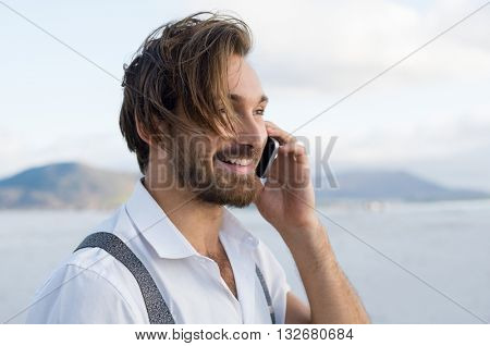 Handsome man in a telephonic conversation at beach. Happy man talking on smartphone at beach. Cheerful guy receiving some good news through mobile phone.