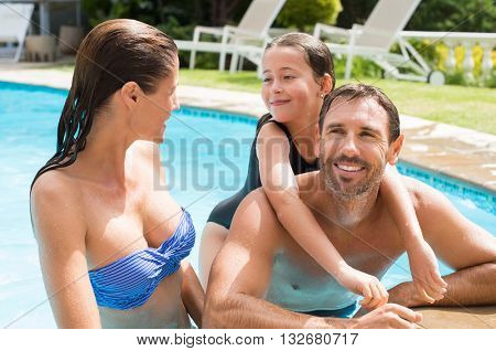 Pretty little girl with her parent in swimming pool outdoor. Family having fun in swimming pool. Portrait of a young family enjoying vacation in a resort.
