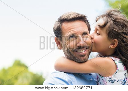 Portrait of a little girl kissing her dad on cheek. Pretty girl giving a kiss to her father outdoor. Loving child embrace and kissing her father. poster