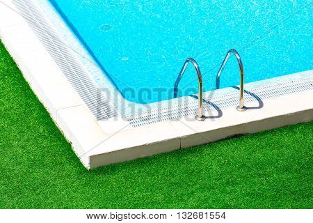 Swimming pool with stair at hotel close up.Beautiful swimming pool with green grass around.Swimming pool with blue clear water.