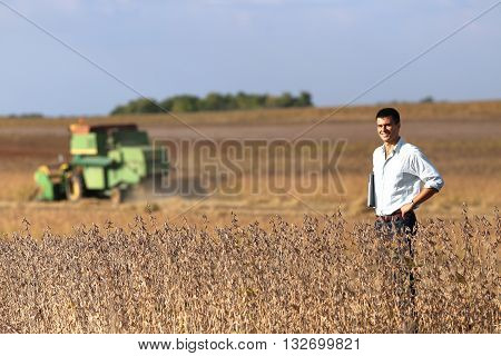 Farmer In Soybean Field With Combine Harvester