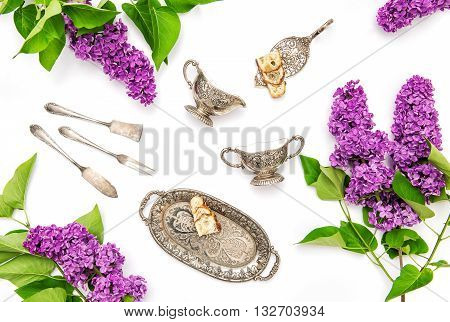 Lilac flowers. Coffee tea cake silber dishes. Flat lay floral background