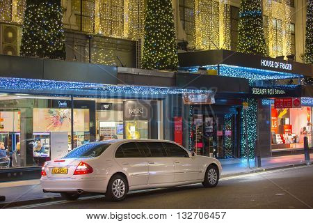 LONDON, UK - DECEMBER 30, 2015: Limousine service car in front of Oxford street department store entrance during Christmas sale