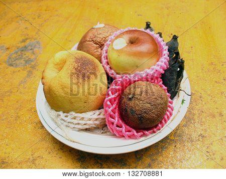 rotten fruit on yellow cement texture ,