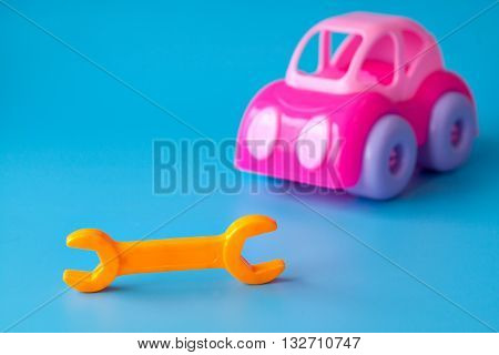 Pink toy car made of plastic on a blue background. Toy wrench orange. Playing in the car repair shop. Copy space.