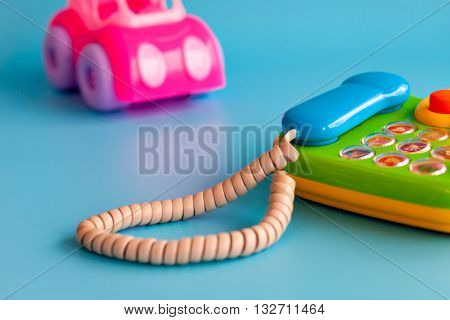 Pink toy car made of plastic on a blue background. And handset. Plastic toy phone. Playing in car repairs. Call mechanic and repair the machine. Copy space.