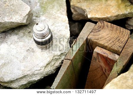 A Metal Component Against A Stone And Wood Background