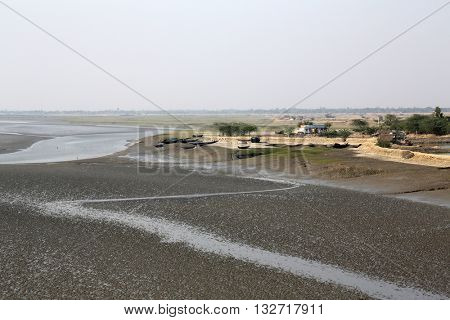 CANNING TOWN, WEST BENGAL, INDIA - FEBRUARY 13: Mud beds on the river Malta during low tide the water in the Canning Town, India on February 13, 2014.