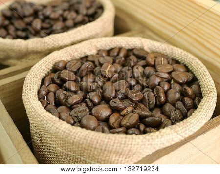 Coffee beans in brown bag sack on wooden table. (selective focus)