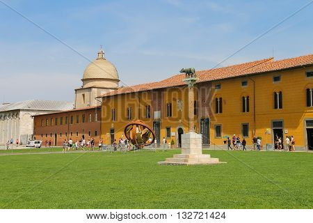 Pisa Italy - June 29 2015: Tourists walking on Piazza dei Miracoli in historic centre. Province Pisa Tuscany region of Italy