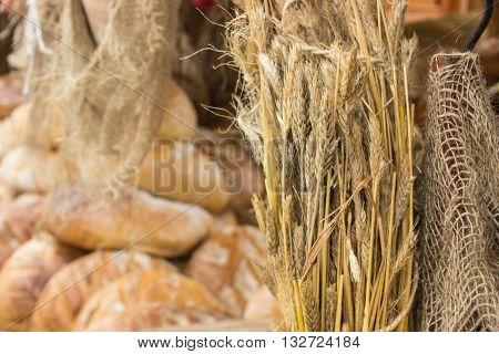 Ears of rye grain and heap of freshly baked traditional loaves of rye bread on stall at the bazaar