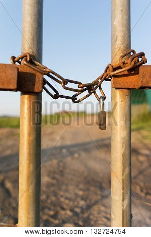 A fence locked wirh a chain and secured by a padlock photographed in vertical format