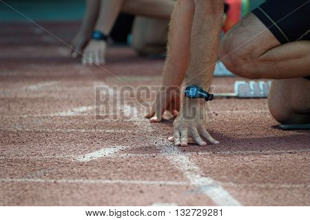 Athletes at the sprint start line in track and field.Hands on the starting line