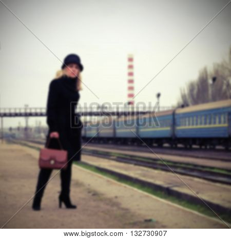 a woman on the platform waiting for a train in a black coat and hat with a bag lady waiting at the train station with a suitcase on the rails background blurred