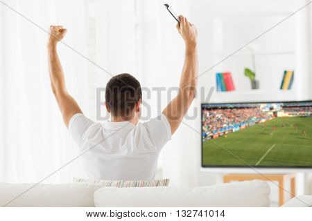 leisure, technology, mass media and people concept - happy man watching football or soccer game on tv and supporting team at home from back