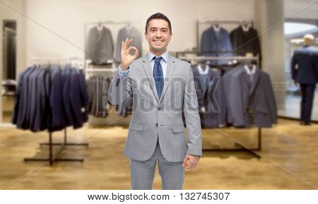 business, people, menswear, sale and clothes concept - happy smiling businessman in suit over clothing store background showing ok hand sign