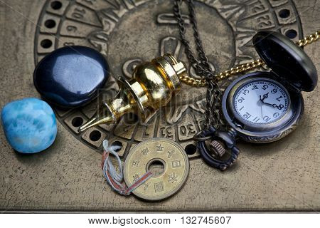 Fortune-telling through astrology. Pendulums with minerals and lucky coin