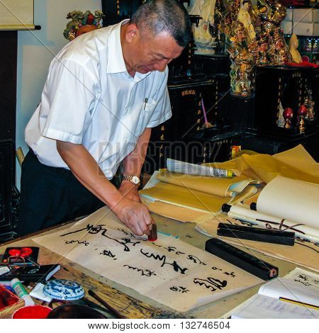 Beijing China - September 19 2011: A man practicing the ancient art of Chinese calligraphy