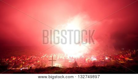 red fireworks above small mountain village in bulgaria