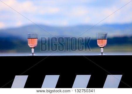 two glass with rose wine over the sunset near mountain lake romance for two conceptual landscape