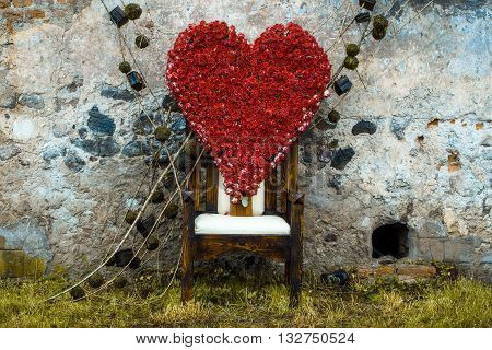 Floral arrangement with red rose flowers in shape of heart on chair outdoor on stony wall background