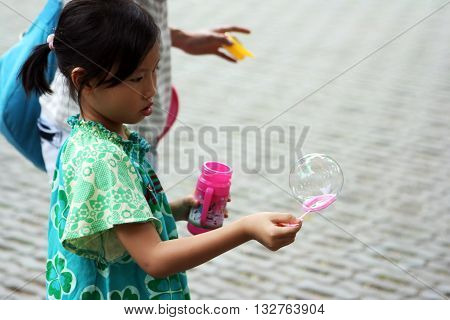 Beijing. China. - August 20, 2009 - The peoples of the world. Chinese girl making soap bubbles The streets of China in August 20, 2009 in Beijing. China.