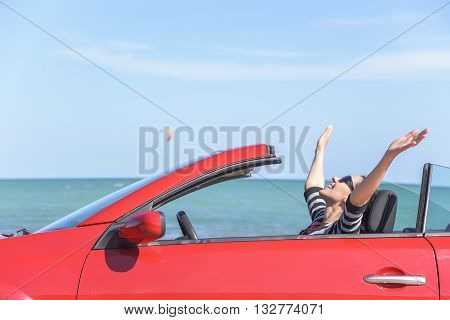 Summer car trip vacation . Woman in red car at background of sea water. Travel, freedom and holidays concept.