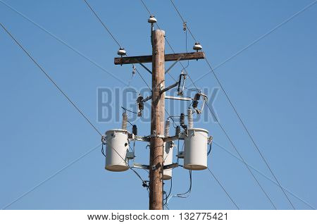 Wooden power utility pole and clear blue sky.