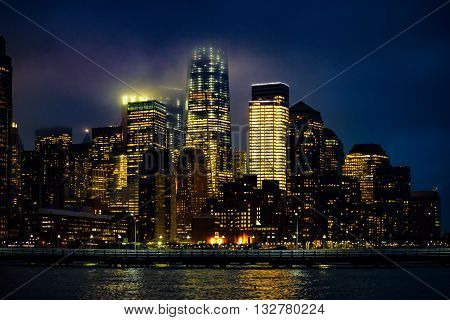 Lower Manhattan and part of the Hudson River on a cloudy night.