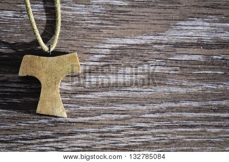 Wooden Tau pendant on the wooden floor