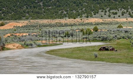 a rusty car frame sits beside the Sevier River in Utah