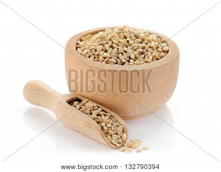 Pearl barley in wooden bowl isolated on white background