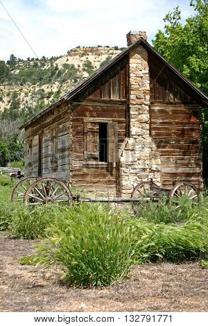 a wagon frame parked next to an old log cabin in Utah