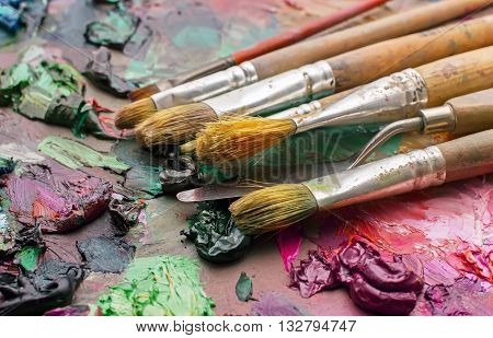 Used Brushes In An Artist's Palette Of Colorful Oil Paint For Drawing