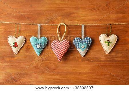 five hearts made of cloth on wood background