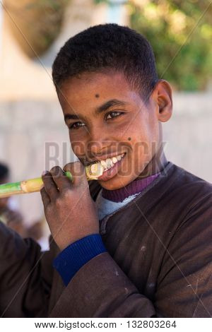 ASWAN, EGYPT - FEBRUARY 7, 2016: Portrait of Nubian boy eating sugar cane.