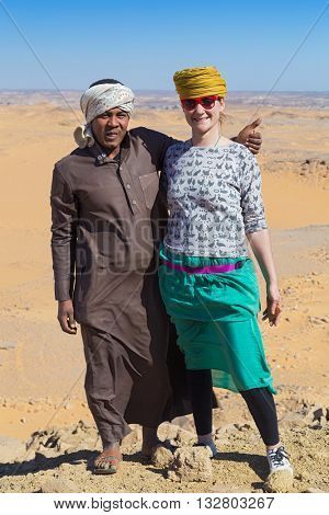 ASWAN, EGYPT - FEBRUARY 7, 2016: Nubian man wearing traditional clothing posing with european tourist.