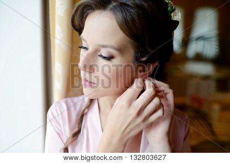 Beautiful Bride In White Wedding Dress Puts On Earring. Beauty Model Girl Is Wearing Jewelry. Female